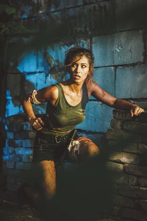 Beautiful young woman with gun in abandoned ruin.