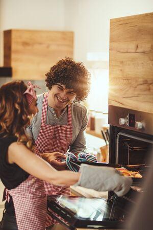 Młoda uśmiechnięta szczęśliwa para wkłada pizzę do piekarnika do pieczenia, śmiejąc się.