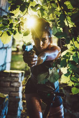 Beautiful soldier woman holding gun and getting ready for the attack in nature.