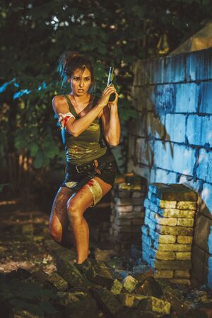 Beautiful young woman holding gun and getting ready for the attack in abandoned ruin.