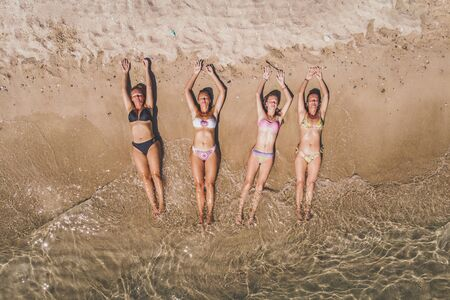 Aerial shot of a four beautiful female friends dressed in a bikini that is enjoying in sunbath on the sandy beach. They are is relaxing at summer vacation in clear sea waves.