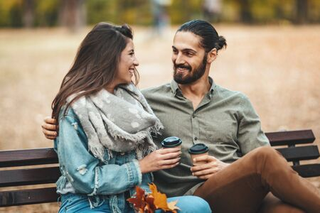 Beautiful smiling couple enjoying in sunny city park in autumn colors looking each other. They are sitting on the bench and having fun.