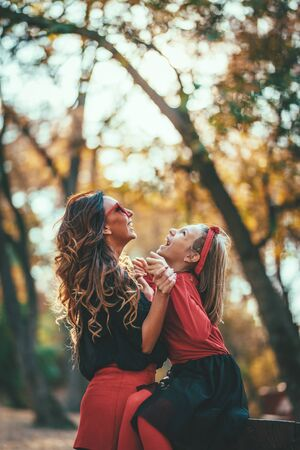 Beautiful young mother and her happy daughter having fun in the forest in sunset. They are hugging each other and smiling.
