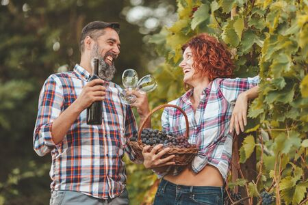 Beautiful smiling couple is having fun and tasting wine at a vineyard. A man is holding a bottle of wine and a woman is holding basket with grapes.