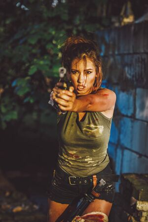 Beautiful young serious woman holding gun and getting ready for the attack in abandoned ruin. Banque d'images