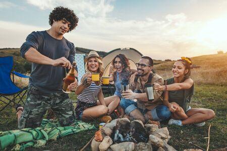 Amigos jóvenes felices disfrutan de un buen día en la naturaleza. Están asando salchichas, comiendo, bebiendo champán, riendo y hablando felices de estar juntos.