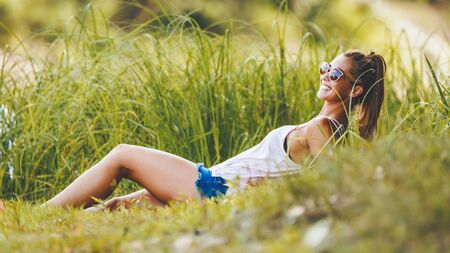 Beautiful young woman enjoying summer, relaxing and dreaming near the lake fringed with lush scenery.