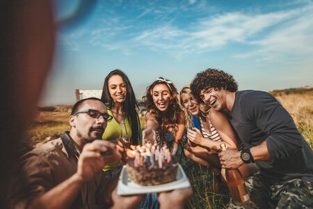 Young people have a good time in camp in nature. Theyre celebrating a birthday, laughing and greeting to their friend with birthday cake, happy to be together. Stock Photo