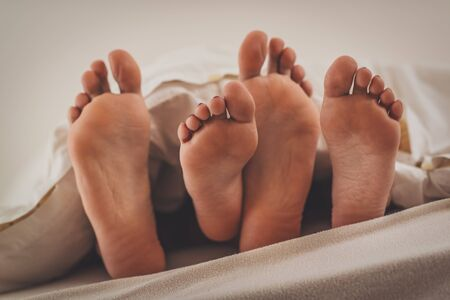 The feet of a couple under the covers in bed.