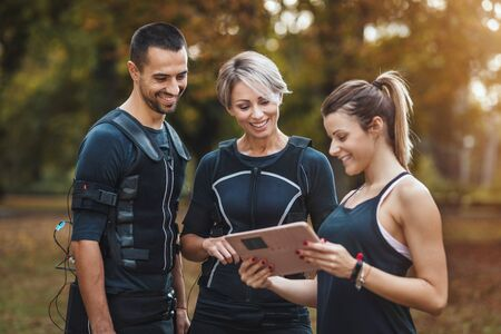 Personal trainer is teaching a confident smiling fitness couple to workout with ems device in the city park.
