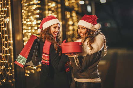 Two female friends enjoy the winter night and laughing with shopping bags and red box in their hands. Stockfoto
