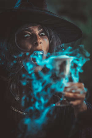 Portrait of witch with awfully face in creepy surroundings and smoky green background drinks magic potion from the goblet.