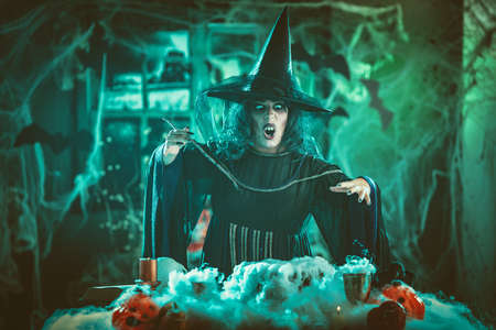 Witch with awfully face and hat on her head in creepy surroundings full of cobweb sends evil. Halloween concept.