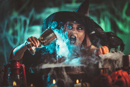 A witch in foggy surrounding holds a goblet above boiling water for a cooking poison soup.