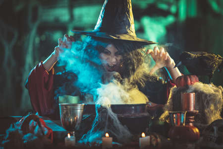 Close-up of young witch with awfully face in creepy surroundings full of steam and fog, tells evil words to magic potion.
