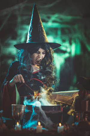 Young witch with awfully face in creepy surroundings full of steam and fog, tells evil words to magic potion.