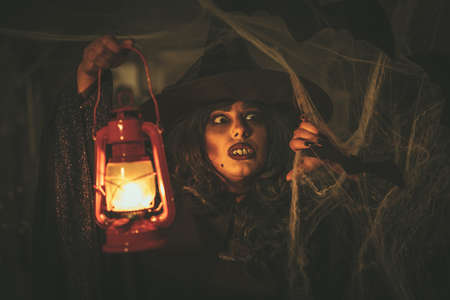 Portrait of witch with awfully face and lighted lantern in her hand in creepy foggy surroundings sends evil.