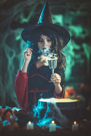 Young witch with seriously face in creepy surroundings and smoky green background holds a goblet with magic potion.