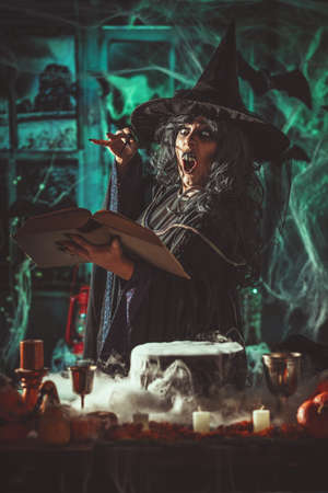 Witch with awfully face in creepy surroundings and smoky green background reading recipe of magic drink.