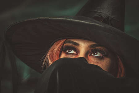 Portrait of witch with awfully face, covered with black scarf, who thinks of what to do next.