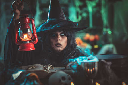 Witch with awfully face in creepy surroundings and smoky green background talks magic words to bones above boiling cauldron. Halloween concept.