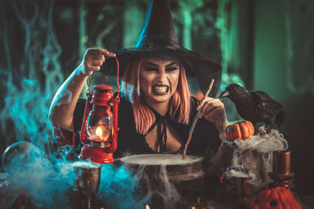Witch with with awfully face and lighted lantern in creepy surroundings cooks poison soup in boiling cauldron.