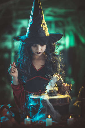 Young witch with angry evil face holds a goblet with magic potion in one and magic wand in the other hand.