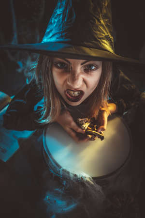 Young angry witch with awfully face tells evil words, and putting bones in cauldron with poison potion.