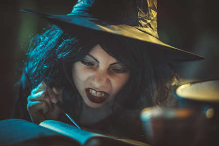 Witch with awfully face reading recipes of magic drink in creepy surroundings and smoky background.