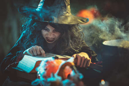 The young witch with awfully face is reading recipes of magic drink in creepy surroundings and smoky background.