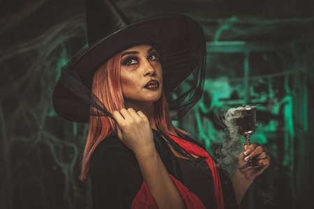 Witch with awfully face in creepy surroundings and smoky green background drinks magic potion from the goblet.