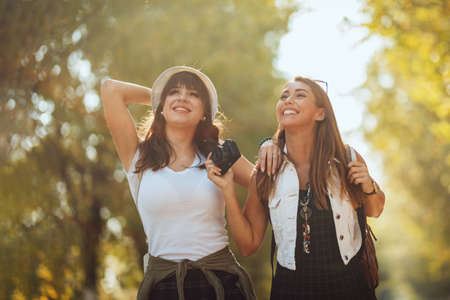 Two beautiful young smiling women with backpacks on their back are walking along the autumn sunny avenue and looking away. Banque d'images