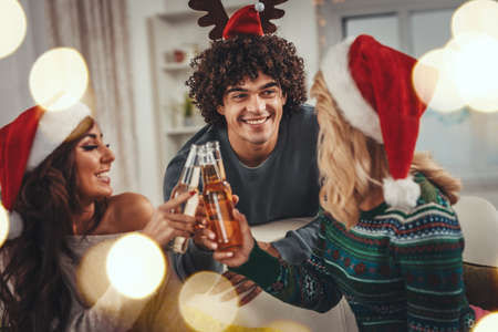 Cheerful young friends dressed in cozy warm sweaters are spending time in the living room on Christmas - New Year eve, smiling, having fun and enjoying with beer.