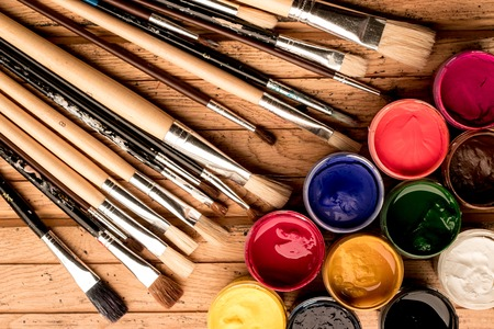 Learn how to paint. Multicolored gouache paint in open containers and artistic brushes on a wooden background - top view