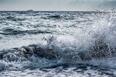 Sea wave splash on stormy day with a ship on a horizon background. Pontecagnano beach, Italy