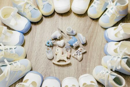 Baby blue bootees circle frame with small cute accesories on wooden background for boy newborn birthday shower party, store add or post card. Top view. Copy space. Reklamní fotografie