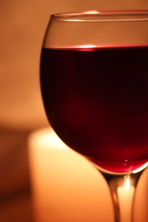 Blurred soft focus bokeh of glass full of red wine glowing from candle light winery background.