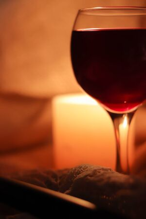 Blurred soft focus bokeh of glass full of red wine glowing from cadle light winery background. Copy space