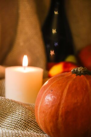 Happy Thanksgiving post card. Autumn holidays still life. Home warmth orange pumpkin close up with white soft warm candle light, fruits and bokeh in stars shape on wine bottle on sackcloth background. Stock fotó