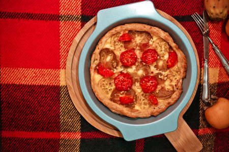 Persimmon and red figs fichi di indica fruit autumn pie with sweet cheese in round baking form on wooden board on checkered woolen red and yellow plaid textile background, top view with space for text