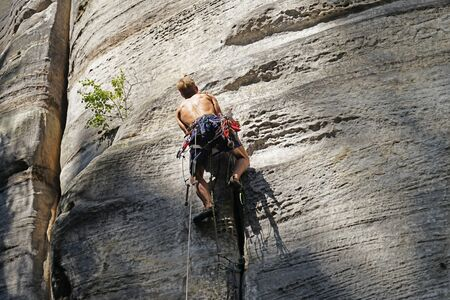 Rock climber hanging on difficult sandstone wall