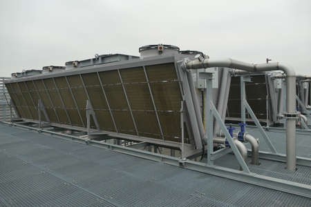Industrial V-shaped air coolers with fans cooling hot refrigerant on roof used in warehouse of food industry Stock Photo