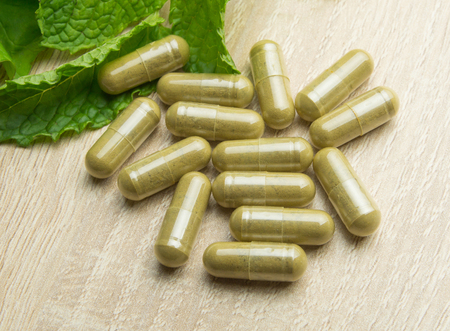 Herbal pills with healthy medical plant. Green leaf, alternative drug on wood ground Stock Photo