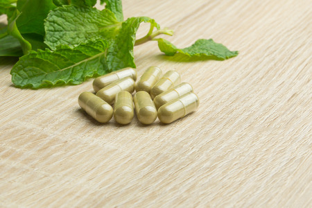 knowlage: Herbal pills with healthy medical plant. Green leaf, alternative drug on wood ground Stock Photo