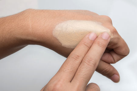 Close up Asia woman testing and choose color of foundation in her hand Stock Photo