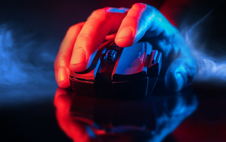 Close up of Hand over wireless Game Mouse on dark background and smoke ; The finger ready to click 스톡 콘텐츠