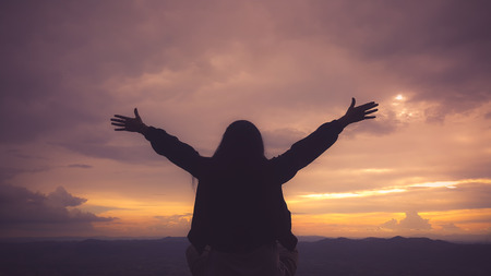Silhouette freedom woman rise hands up to welcome a good day , open arms motivate enjoy and success the wish 版權商用圖片