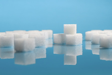 selective focus Group of Sugar cubes vary position on light blue background Archivio Fotografico