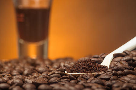 Close up cofee powder in the white spoon over coffee beans withe coffe cub as background Stockfoto