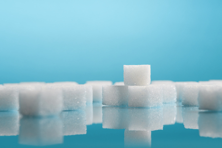 Group of Sugar cubes vary position on light blue background